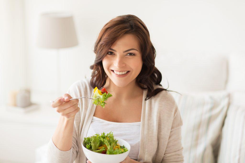 Interior de una casa en la que una mujer se come una ensalada